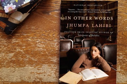 In Other Words by Jhumpa Lahiri against a wooden backdrop with a pile of books/journals in upper left corner.